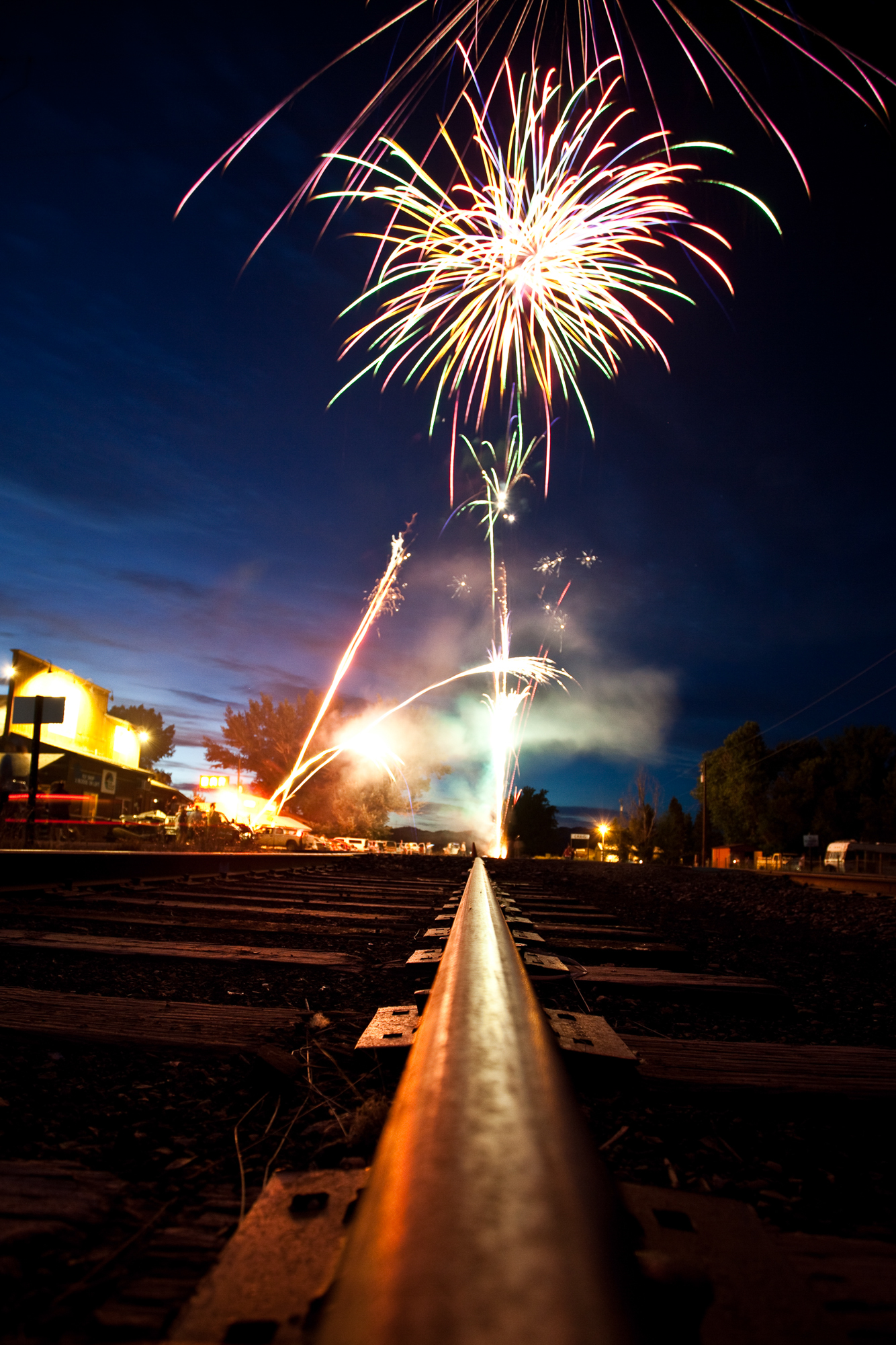 Looking down the tracks. Come dark, well after 11PM, the fireworks begin in celebration of Independence Day. Looking down the abandoned train tracks running through town to Joe's Bar, the scene of the action, shadows can be seen running in the dim light from the fireworks.
