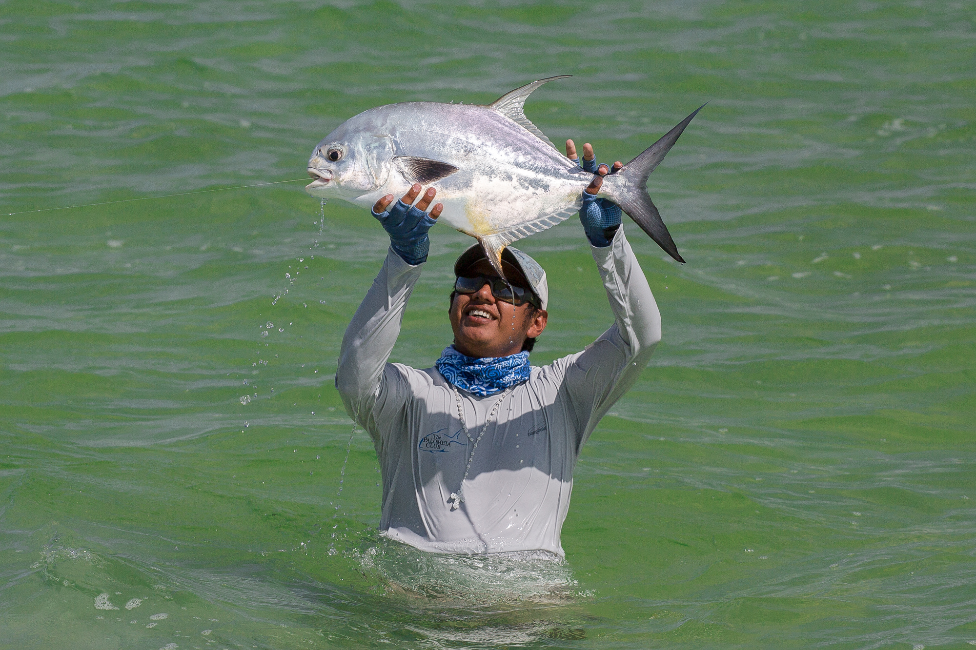 (2/3) Every permit is celebrated, but this one perhaps more so. After a week of tough weather and morning encounter that saw a securely hooked permit broken off by a certain over-zealous angler, the cradling and hoisting of this fine specimen brings a collective sense of elation to both guides and anglers. (photo: Chad Shmukler)