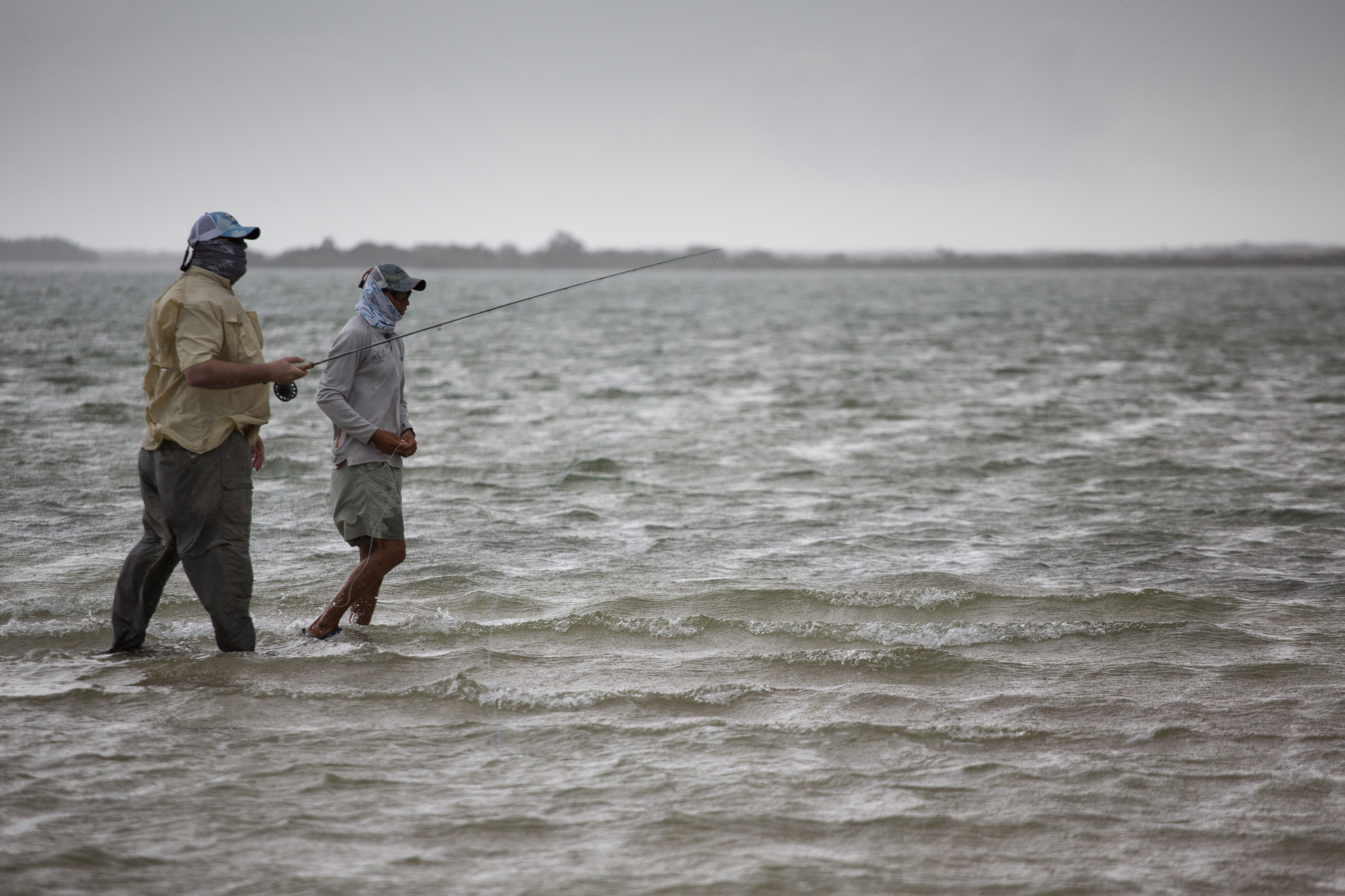 (1/3) Storms roll in only moments after arriving on a prime bonefish flat. Yet, despite steady rain and entirely flat light, guide Arun spots a few cruising bonefish 25 yards off. A couple of casts and backing runs later, a healthy bonefish comes to hand (photo: Chad Shmukler).