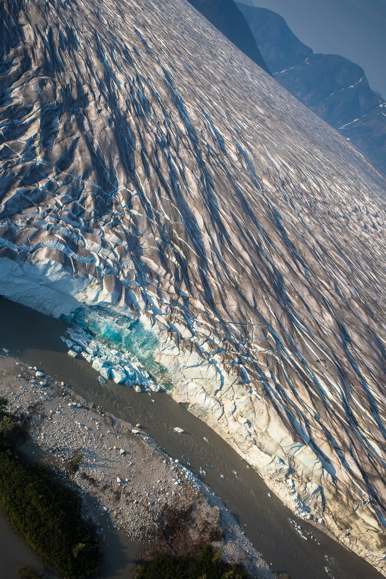 Iridescent blue ice is revealed as a small portion of the Taku Glacier, near the glacier's snout, calves into the grey meltwater below (photo: Chad Shmukler).