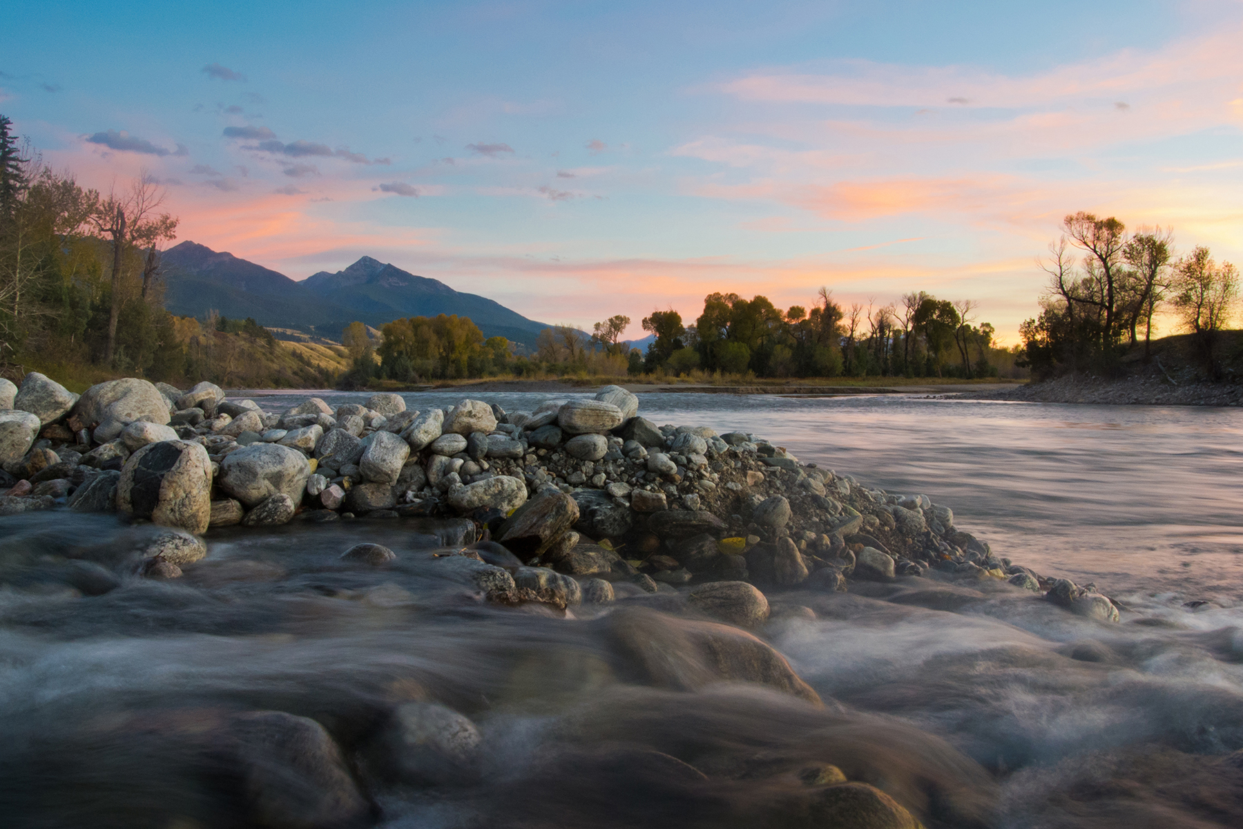 The sun sets on the iconic Yellowstone River in this nicely framed landscape.