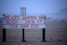 no lifeguards sign on beach
